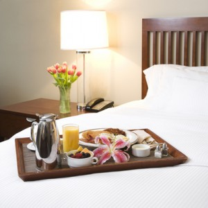 Breakfast tray on white bed.